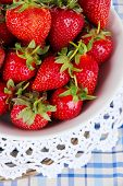 Strawberries in plate on wicker stand on napkin close-up