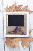 Wooden frame with dried flowers, leaves and old blank photo on wooden background