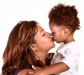 Portrait of cheerful mother kissing baby, studio shot, happy motherhood, lovely African family, happ