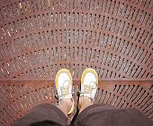 a shot of yellow and white boat or deck shoes on a rusty grate