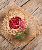 Fresh And Dried Pink Pepper In A Small Basket