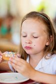 Adorable little girl enjoying eating donut at cafe