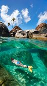 Split photo of young woman snorkeling in turquoise tropical water among huge granite boulders at The