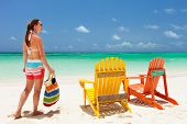 Young woman enjoying vacation at tropical beach with two colorful wooden chairs on white sand and tu