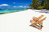 Two bamboo chairs on a beautiful tropical beach with white sand and clear turquoise ocean at exotic