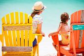Back view of mother and daughter family sitting on colorful wooden chairs at tropical beach enjoying