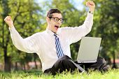 Young man cheering and watching TV on a laptop in park on a sunny day
