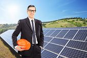 Construction worker in front of solar panels, outdoors