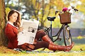 Young woman with bicycle sitting on a green grass and reading a newspaper in park
