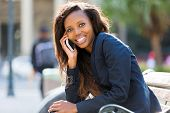 cheerful african businesswoman using smart phone outdoors