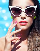Colorful portrait of young attractive woman wearing sunglasses by the swimming pool, summer beauty a