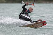 Professional  Kitesurfer Jumps Over The Water During Training On Lake Of Santa Croce
