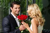 Handsome man with bunch of red roses dating his lady