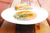european cuisine: vegetable soup served with toasts on white dish on wooden table