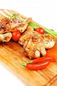 meat food : roasted chicken legs garnished with green sprouts and peppers on wooden plate isolated o