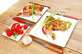 meat food : chicken legs garnished with green peas and and cutlery on white plates over wooden table