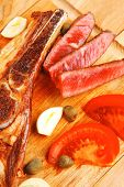 fresh roasted beef meat steak sliced on wooden board with red hot pepper cutlery isolated  over whit