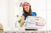 foto of laundry  - Young beautiful woman standing with basket laundry for ironing - JPG