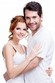Portrait of beautiful attractive happy couple embracing over white background.