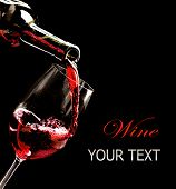 Wine. Red wine pouring into wine glass from the bottle. Isolated on black background. Art border design with space for your text