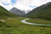 stock photo of floating  - River floats slowly through grass field to the mountain. over the mountain slowly floating clouds