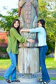 Two Young, Biracial Teen Girl In Park Hugging A Totem Pole On Sunny Day