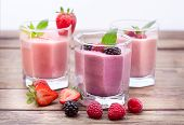 Smoothie drinks from summer berries on the wooden table