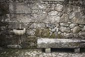 ancient wall made of stones with water supply and a stone bench