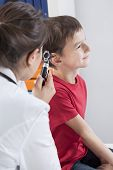 stock photo of otoscope  - Young pediatrician checking the little man by otoscope - JPG