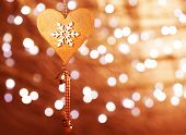 Beautiful wooden heart shaped New Year decoration with snowflake ornament hanging on blur shiny golden background, stylish christmastime bauble