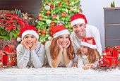 Cheerful parents with two cute smiling kids lying down near Xmas tree at home, celebrating Christmas, festive greeting card, happy family holiday concept