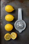 High angle shot of a group of lemons, three whole and one cut, on a metal baking sheet with an old fashioned juicer. Horizontal format.