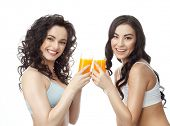 closeup portrait of two attractive  caucasian smiling woman brunette isolated on white studio shot lips toothy smile face hair head and shoulders looking at camera tooth drinking orange juice