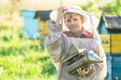 Teenage Beekeeper Working In Apiary