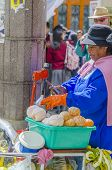 LA PAZ, BOLIVIA, MAY 9, 2014:  Local woman prepares fresh orange juice on street stand