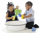 image of tub  - A young brother and sister having fun playing in a tub full of water and water toys - JPG