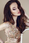 picture of wearing dress  - fashion studio portrait of beautiful young girl with dark hair wearing luxurious beige dress - JPG