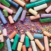 Collection Of Rainbow Colored Artistic Pastel Crayons With Pigment Dust On Old Desk.