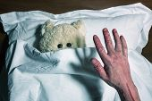 Scared teddy bear laying in bed