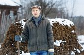man with fork in of manure early spring