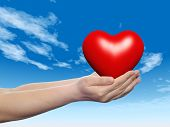 Concept or conceptual 3D red abstract heart sign or symbol held in hands by a woman or child over a nice blue sky background