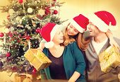 Happy Christmas Family with Christmas gifts. Smiling Parents with teenage daughter at Home Celebrating New Year. Christmas Tree