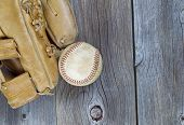 Used Baseball And Worn Glove On Old Wood