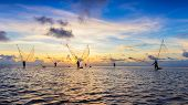 Colorful Sunset Or Sunrise Landscape With Silhouettes Of Fishermen On The Beach Of Bac Lieu, Vietnam