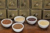 gluten free grains (amaranth, millet, quinoa, brown rice, teff  in small ceramic bowls with a rustic drawer cabinet in background