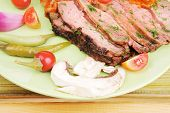 beef slices on plate over wooden table