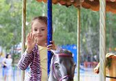 Beautiful little girl spinning on the carousel in the park.