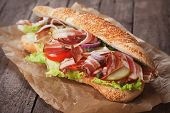 Submarine sandwich with bacon, pickles, tomato and lettuce salad