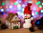 stock photo of gingerbread house  - gingerbread house over and lovely handmade snowman - JPG