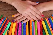 Multicolor female manicure with markers and pencils on wooden background